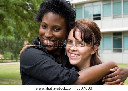 smiling female students in front of academic building - stock photo