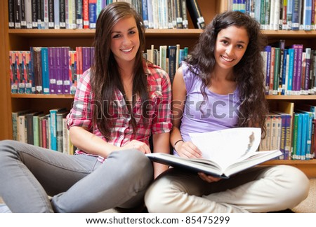 Smiling female students with a book in a library - stock photo