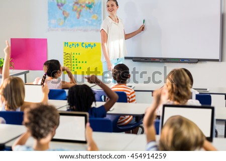 Smiling female teacher teaching students using whiteboard in classroom