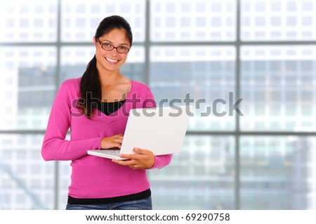 Smiling female teenage student with long brown hair holding a laptop computer. Horizontal format standing in front of a large bank of windows.
