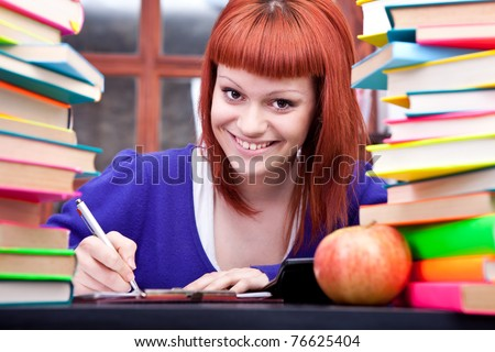 smiling female teenage student with red hair seated at desk between stacks of books