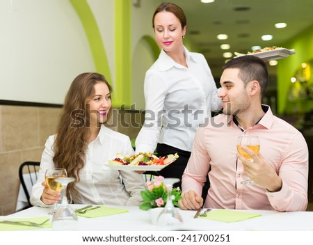 Smiling female waiter with plates serving guests table in cafe. Focus on girl  - stock photo