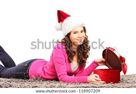 Smiling female with christmas hat lying on a carpet and opening a present isolated on white background - stock photo