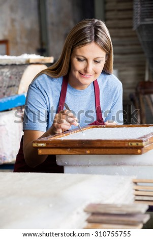 Smiling female worker cleaning paper on mold with tweezers in factory - stock photo