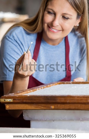 Smiling female worker removing large fibers from paper with tweezers in factory - stock photo