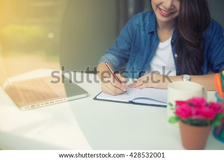 smiling female writing on notebook by laptop on white table - stock photo