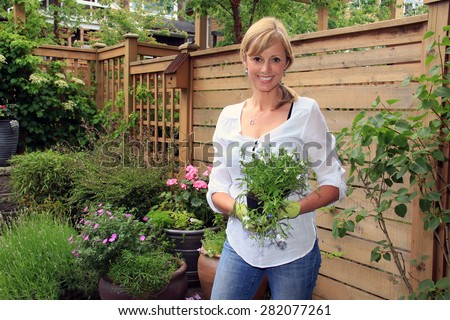 Smiling fifty year old lady gardener outside in the garden holding a pack of lobelia.  - stock photo
