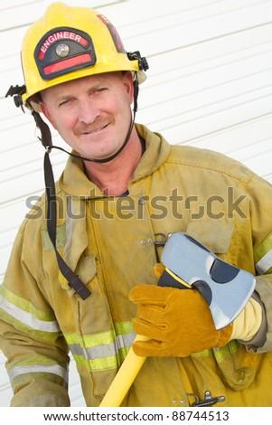 Smiling firefighter man holding axe - stock photo