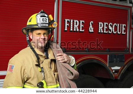 smiling firefighter standing in front of fire engine in uniform holding a fire hose - stock photo