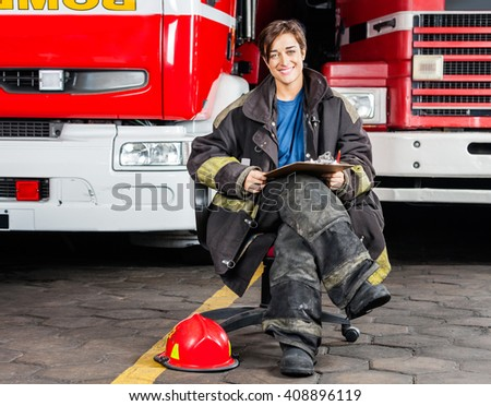 Smiling Firewoman Sitting On Chair Against Trucks - stock photo