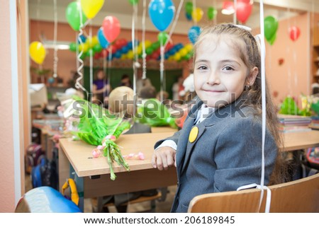 Smiling first grade pupil at the school desk looking back - stock photo