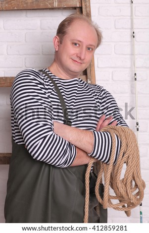 Smiling fisherman in waders with rope - stock photo