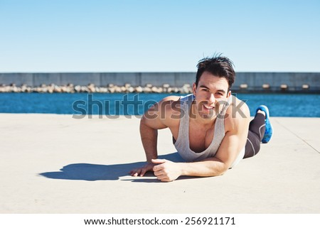 Smiling fit athlete resting outdoors