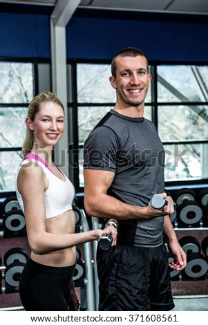 Smiling fit couple lifting dumbbells at gym - stock photo