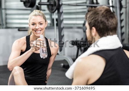 Smiling fit couple sitting at crossfit gym - stock photo