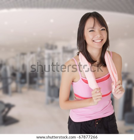 Smiling fit girl holding towel and taking rest in gym. - stock photo