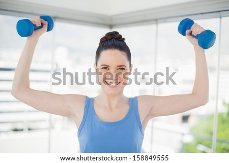 Smiling fit woman exercising with dumbbells in bright sports hall - stock photo