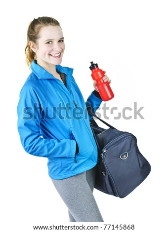 Smiling fit young woman with gym bag and water bottle ready for fitness exercise - stock photo