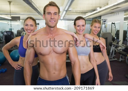 Smiling fitness class posing together at the gym - stock photo