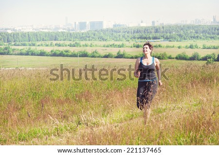 Smiling fitness plus size woman running  - stock photo