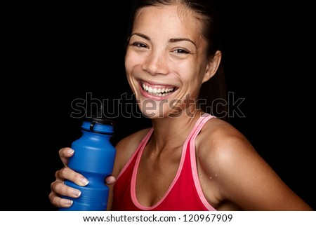 Smiling fitness sportswoman with a blue sport bottle on black background. Multiracial Asian fitness model happy. - stock photo