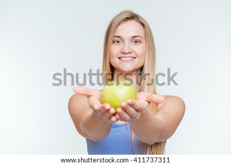 Smiling fitness woman giving apple at camera isolated on a white background - stock photo