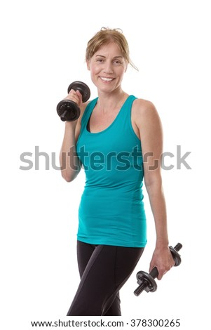 Smiling fitness woman in azure t shirt holds pair of dumbells. Isolated on white background.