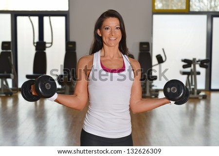 Smiling fitness woman lifting weights - stock photo
