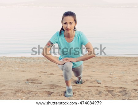 Smiling fitness young woman stretching her legs and preparing to run on sand beach in summer, looking at camera