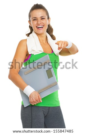 Smiling fitness young woman with scales pointing in camera - stock photo