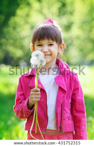 smiling five-year girl with bouquet of dandelions in park