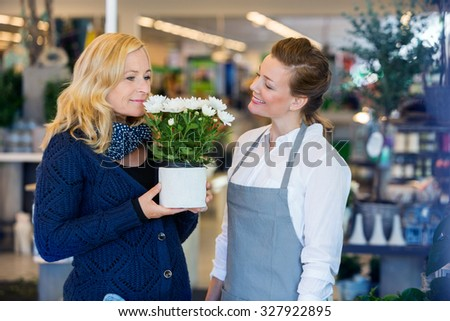 Smiling florist looking at female customer smelling flowers in shop - stock photo