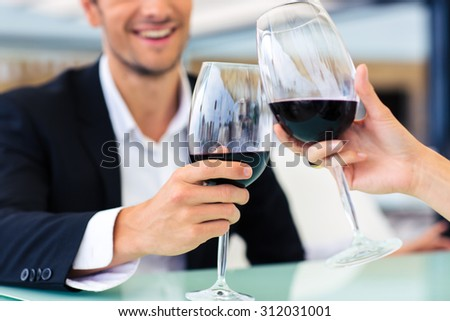 Smiling formal man drinking red wine in restaurant