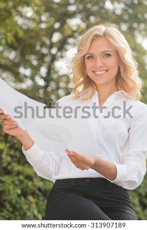 Smiling freelance lady sitting in the park and working. Beautiful woman in white shirt and black trousers looking at the camera. - stock photo