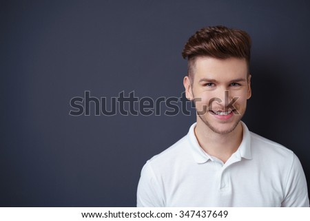 Smiling friendly attractive young man with a modern trendy hairstyle posing against a dark grey background with copyspace, head and shoulders portrait