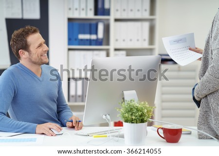 Smiling friendly businessman talking to a co-worker or his secretary who is holding a document as he sits at his desk in the office behind a desktop computer - stock photo