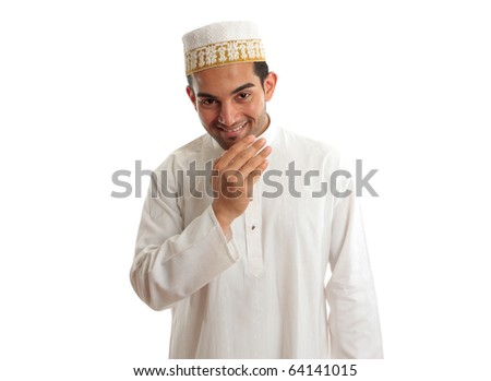 Smiling friendly ethnic man wearing a traditional embroidered robe with ruby buttons and a white and gold embroidered topi hat.  White background. - stock photo