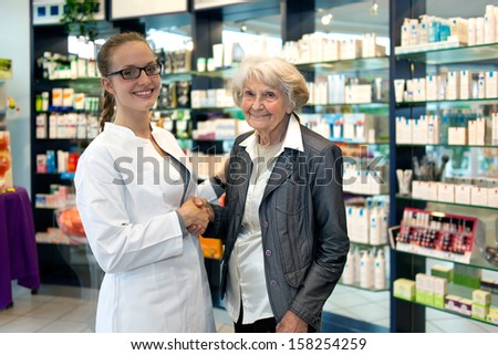 Smiling friendly female pharmacist wearing glasses assisting an elderly lady in her pharmacy or drugstore shaking hands with a lovely smile