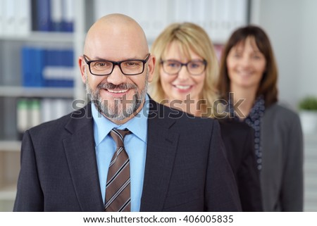 Smiling friendly male business executive wearing glasses standing in the foreground of his successful team of two female co-workers - stock photo