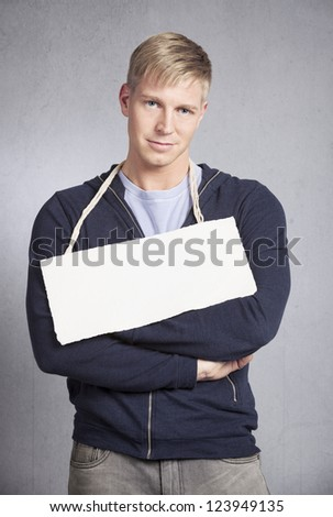 Smiling friendly man holding white empty signboard with space for text  isolated on grey background. - stock photo