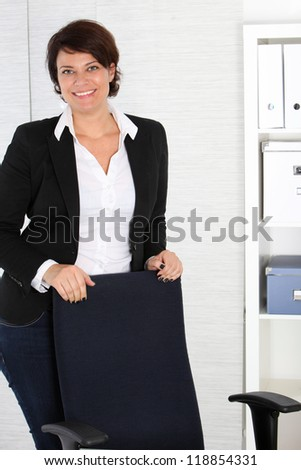 Smiling friendly manageress in a stylish black jacket standing behind her chair in her office - stock photo