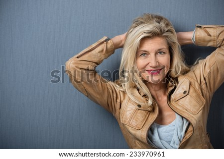 Smiling friendly middle-aged woman standing with her hands clasped behind her head looking at the camera, studio background with copyspace - stock photo
