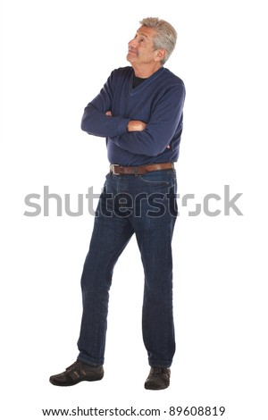 Smiling, friendly senior man in 3/4 full length pose, standing with arms crossed, looking up with eyebrows raised. He wears jeans and v-necked long sleeved shirt. Vertical format isolated on white.