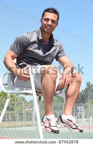 Smiling friendly tennis umpire sitting in the sunshine