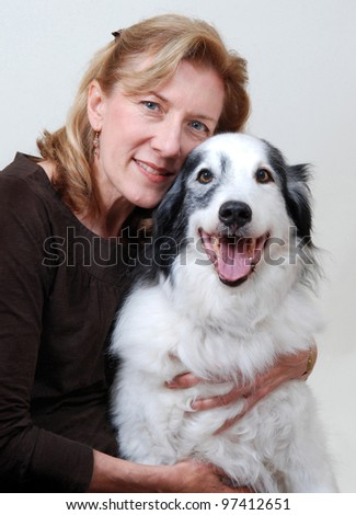 Smiling, friendly woman hugging dog - stock photo