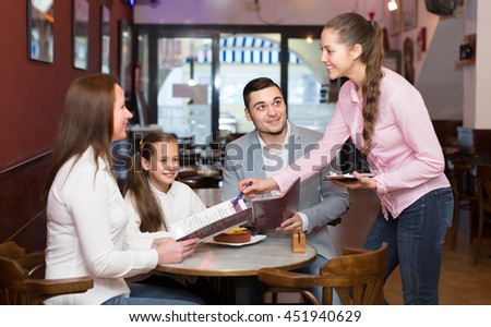 Smiling friendly young waitress serving family of three at cafe table. Selective focus on guy - stock photo