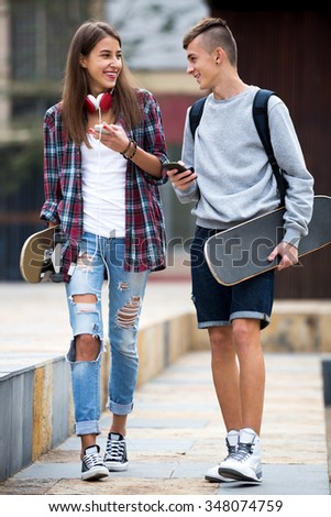 Smiling friends carrying skateboards and walking through city - stock photo