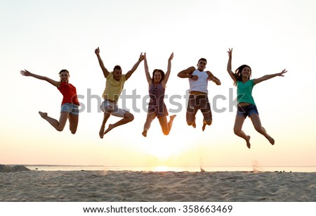 smiling friends dancing and jumping on beach - stock photo