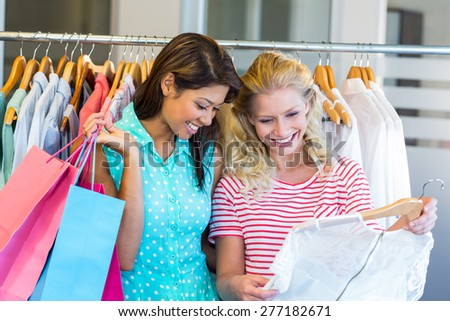 Smiling friends doing shopping together in clothes store - stock photo