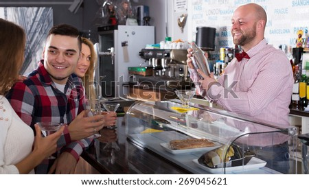 Smiling friends drinking and chatting with cheerful adult barman at bar counter - stock photo